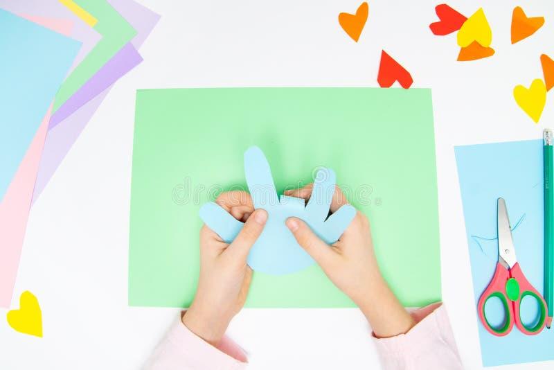 Como fazer o coelho de papel para cumprimentos e divertimento da Páscoa Projeto da arte das crianças Conceito de DIY As mãos das  fotos de stock royalty free