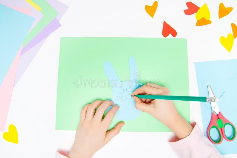 Como fazer o coelho de papel para cumprimentos e divertimento da Páscoa Projeto da arte das crianças Conceito de DIY As mãos das  foto de stock royalty free