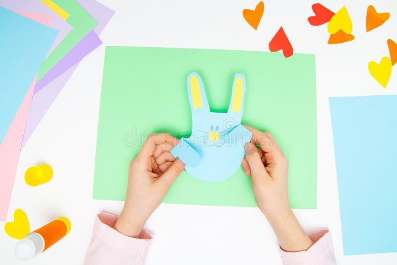 Como fazer o coelho de papel para cumprimentos e divertimento da Páscoa Projeto da arte das crianças Conceito de DIY As mãos das  imagem de stock