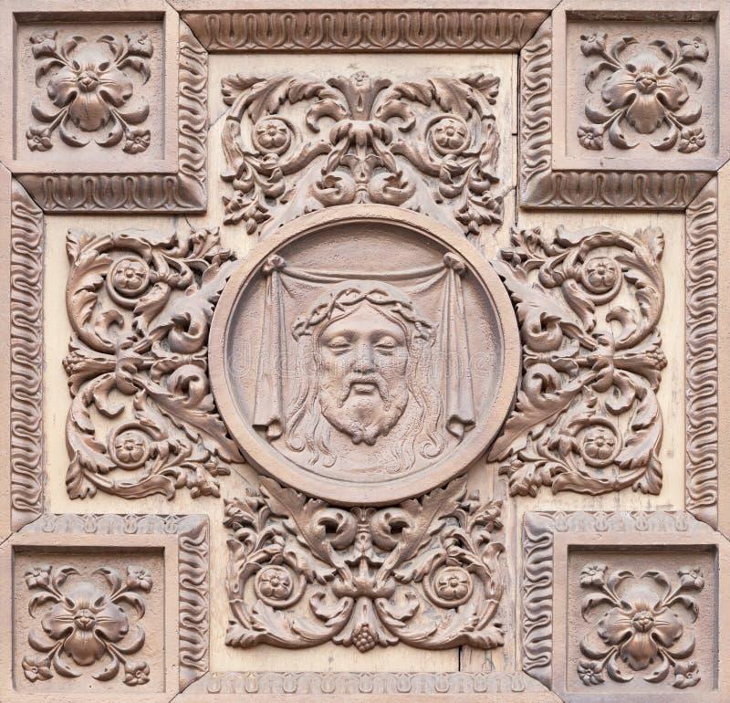 COMO, ITALIA - 8 DE MAYO DE 2015: El metal - relieve de madera con el instrumero de Crucifixión en la puerta de la iglesia Santua fotos de archivo