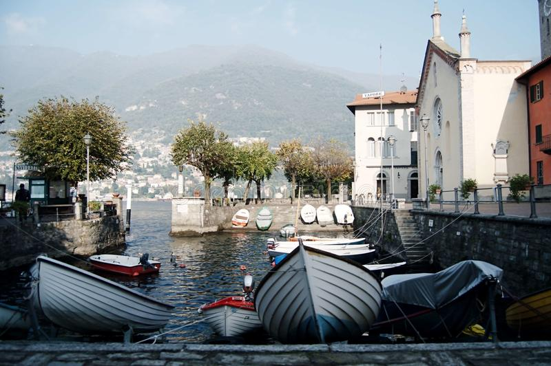 Como, Italien - 2014 Ansicht von See Como an einem nebeligen Tag mit Motorboot und von Hafen in Torno, in einem reizend Dorf zwis stockfotografie