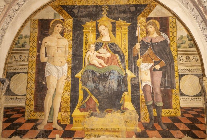 COMO, ITALY - MAY 8, 2015: The fresco of Madonna with the saints Sebastian de Roch in church Basilica di San Fedele. By Andreas de Magistris 1504 royalty free stock photo