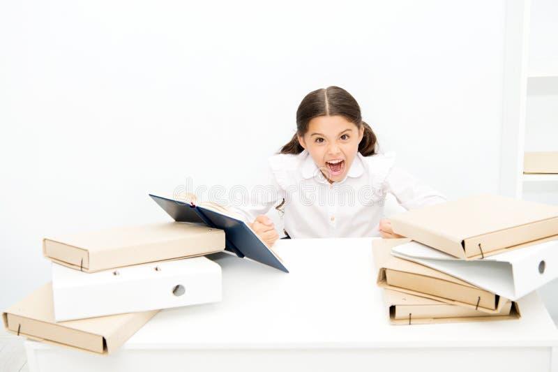 Como una furia El alumno enojado apretó sus manos en los puños La niña no hace como la lectura del libro de la lección en escuela imagen de archivo