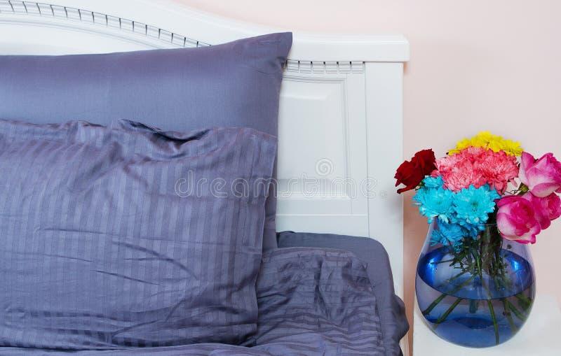 Comodino con il vaso delle rose dei fiori e dell'aria fresca della camera da letto Letto con le tele blu, coperta, cuscini per te fotografia stock