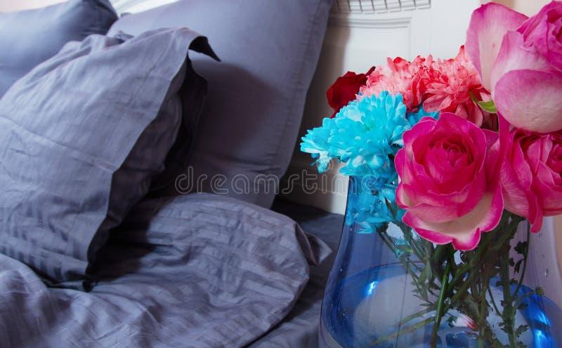 Comodino con il vaso delle rose dei fiori e dell'aria fresca della camera da letto Letto con le tele blu, coperta, cuscini per te fotografia stock libera da diritti