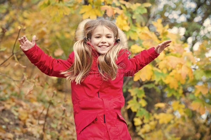 Comodo e spensierato Capelli lunghi biondi del bambino che camminano in rivestimento caldo all'aperto La ragazza felice in cappot fotografia stock