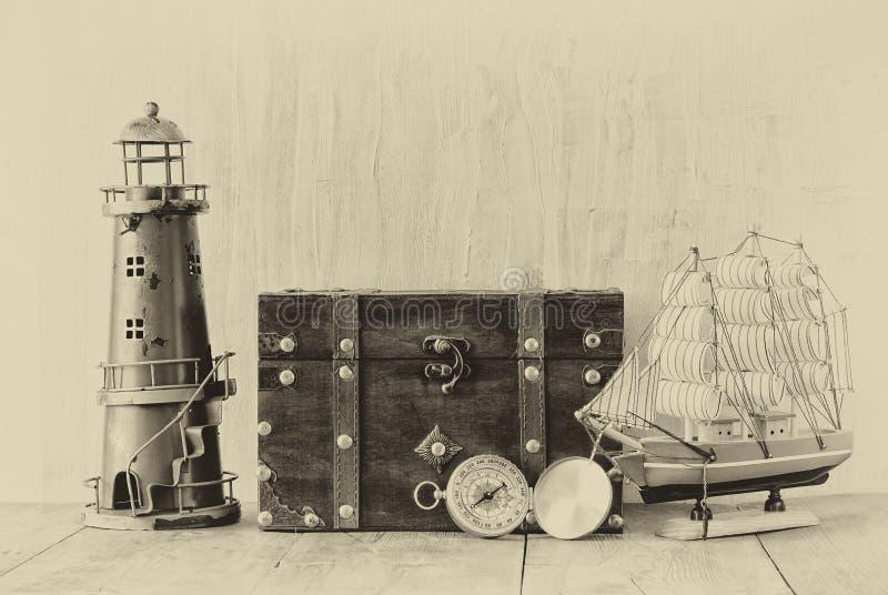 Compás antiguo, faro del vintage, barco de madera y pecho viejo en la tabla de madera foto vieja del estilo blanco y negro imágenes de archivo libres de regalías
