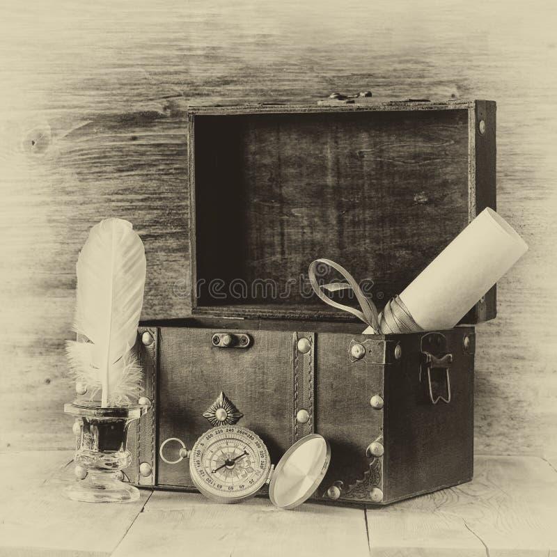 Compás antiguo, tintero y pecho de madera viejo en la tabla de madera foto vieja del estilo blanco y negro imágenes de archivo libres de regalías