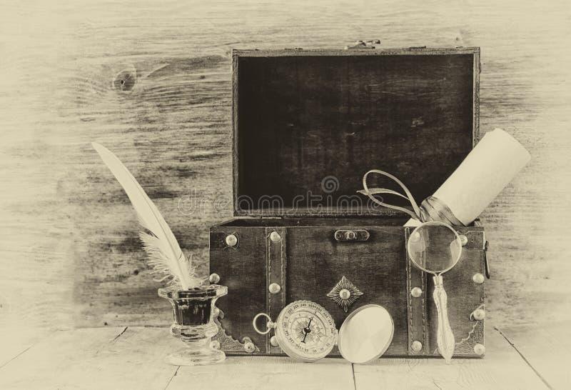 Compás antiguo, tintero y pecho de madera viejo en la tabla de madera foto vieja del estilo blanco y negro imagen de archivo