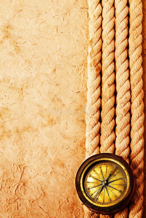 Compás de cobre amarillo antiguo con la cuerda en viejo fondo de papel del vintage Añejo retro fotos de archivo libres de regalías