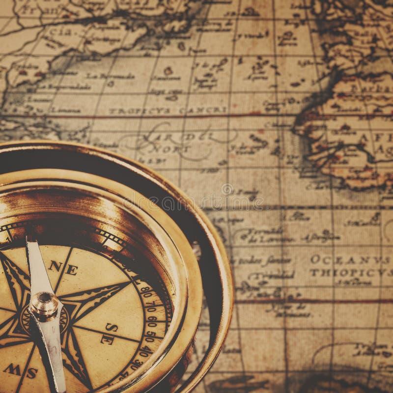 Compás de cobre amarillo retro sobre mapa de papel antiguo imagen de archivo libre de regalías