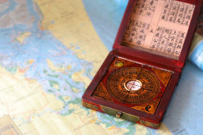 Compás del shui de Feng en una carta náutica imagenes de archivo