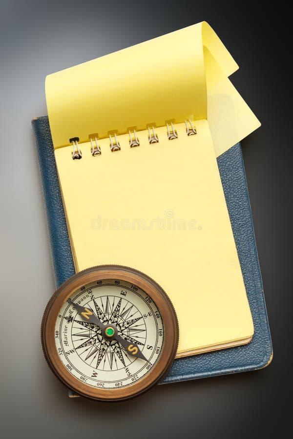 Compás del vintage y libreta amarilla en blanco imagen de archivo libre de regalías