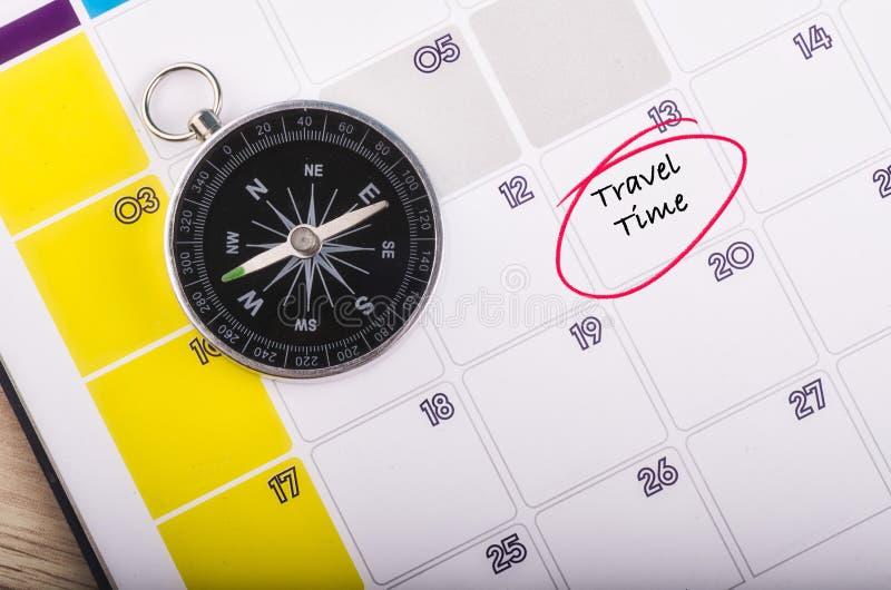 Compás en calendario del planificador con TIEMPO de la palabra VIAJE imagenes de archivo