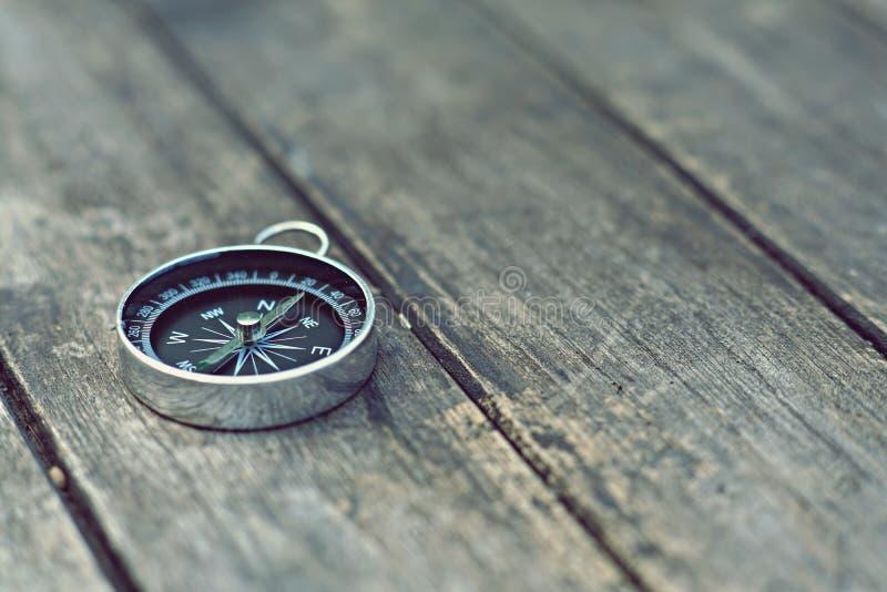Compás en el viejo fondo de madera de la tabla, concepto del viaje, tono del vintage imagen de archivo libre de regalías