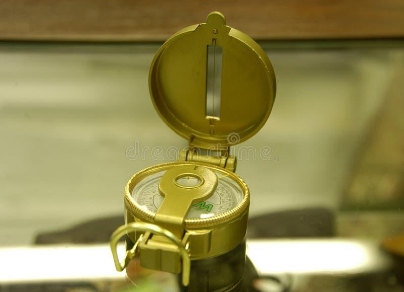 Compás en marco metálico de oro fotografía de archivo
