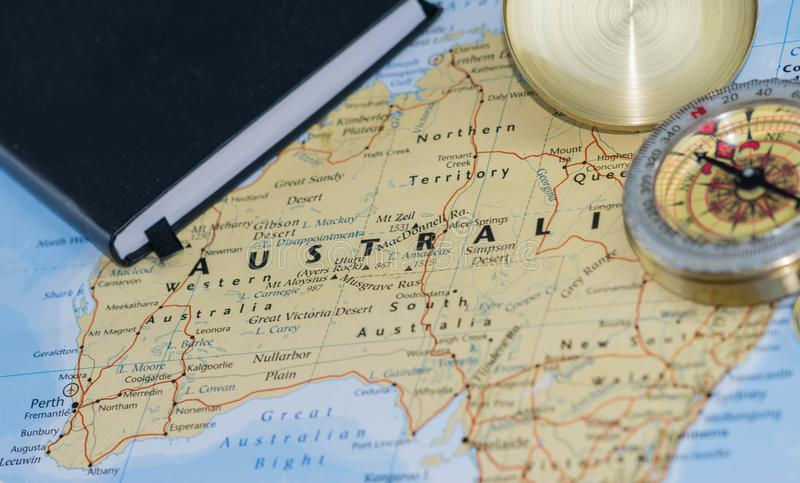 Compás en un mapa ascendente del cierre que señala en Australia y que planea un destino del viaje con las notas del viajero en la fotografía de archivo libre de regalías