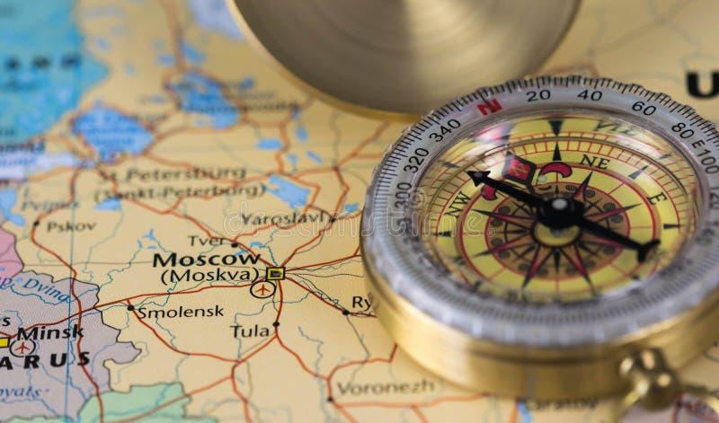 Compás en un mapa ascendente del cierre que señala en Moscú y que planea un destino del viaje foto de archivo