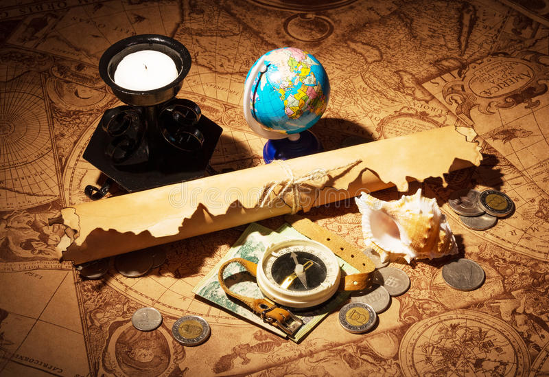 Compás, globo y monedas en los mapas viejos del fondo fotografía de archivo libre de regalías