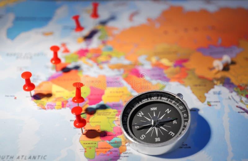 Compás moderno con los pasadores en mapa del mundo imagen de archivo
