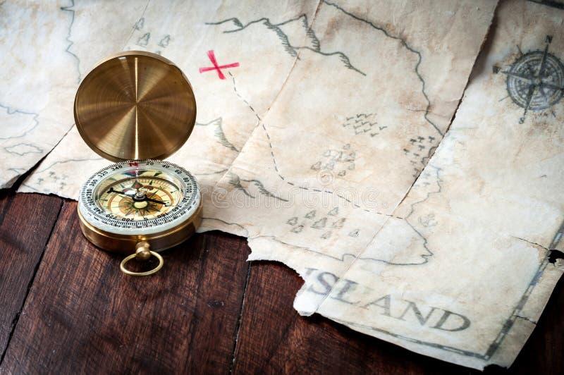 Compás náutico delante del mapa del tesoro de los piratas de la falsificación en la tabla de madera fotografía de archivo