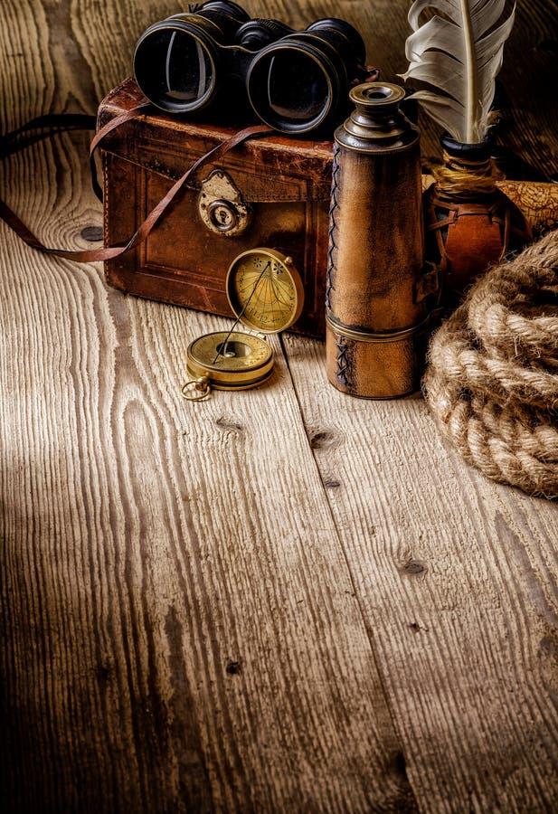 Compás retro, prismáticos y catalejo del viejo vintage en etiqueta de madera fotos de archivo