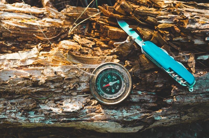 Compás y cuchillo de la supervivencia en un tocón putrefacto viejo Una herramienta para caminar y la supervivencia fotografía de archivo libre de regalías