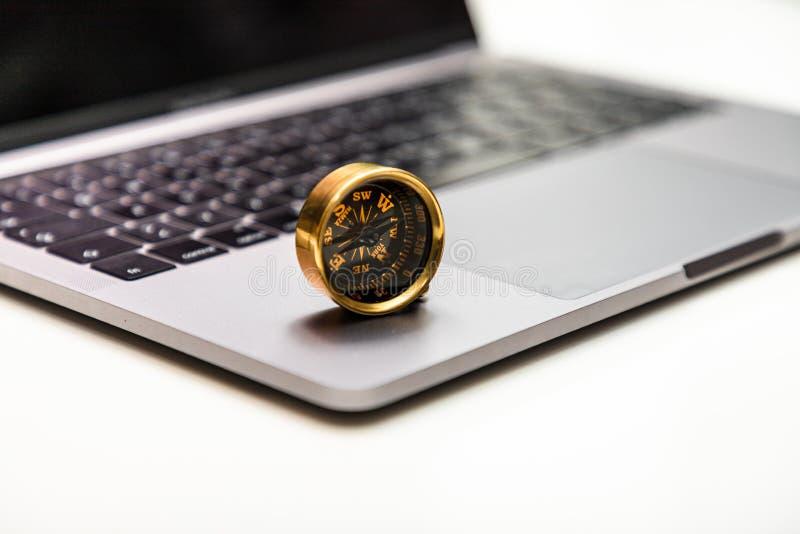 Compás y ordenador portátil como símbolo de la orientación y de metas en el I fotografía de archivo