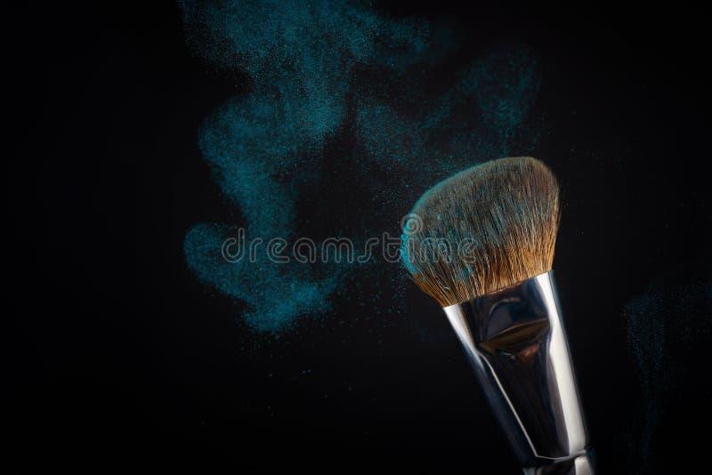 Compõe a escova com o pó azul espirra no fundo preto imagem de stock royalty free