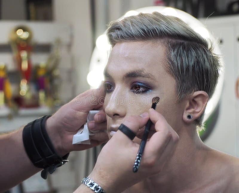 Compõe o artista faz a composição no mordente do modelo masculino novo fotos de stock