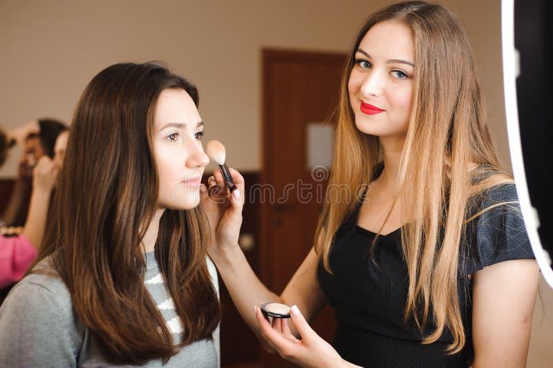 Compõe o artista que faz o profissional para compor da jovem mulher Escola da beleza foto de stock