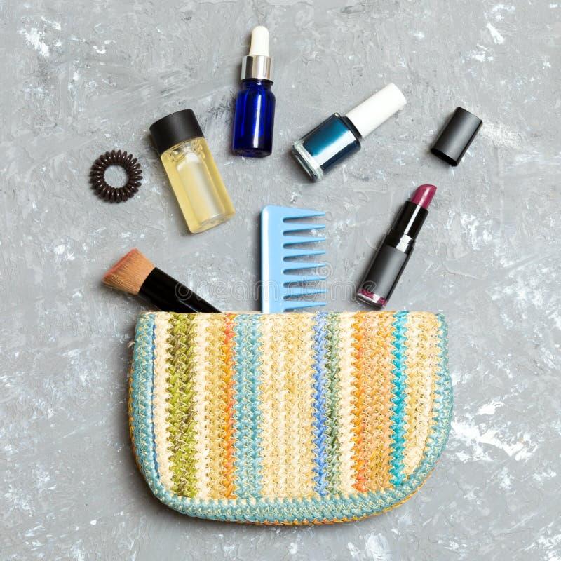 Compõe os produtos que derramam fora dos cosméticos ensacam, no fundo cinzento do cimento com espaço vazio para seu projeto imagens de stock royalty free
