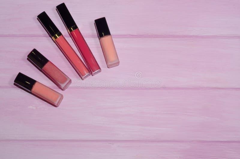 Compõe produtos de beleza no fundo cor-de-rosa Grupo de batons vermelhos e cor-de-rosa Cosméticos decorativos Vista superior, fla fotografia de stock