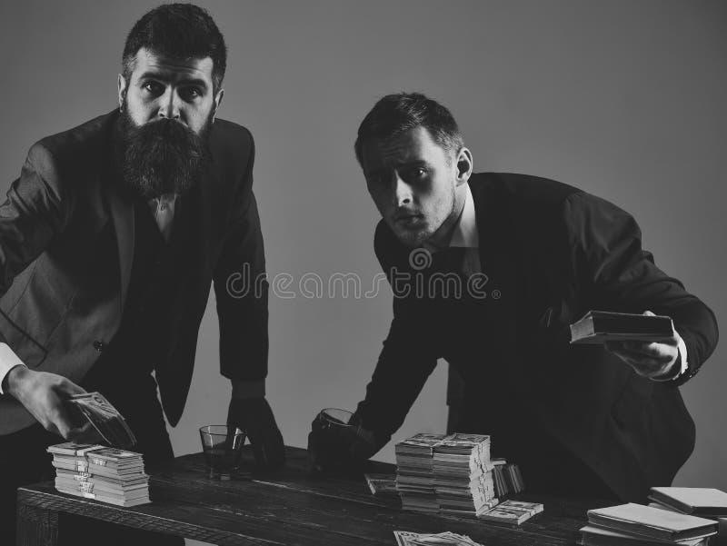 Compañía contratada a negocio ilegal Hombres en la tabla con las pilas de bebidas del dinero y del alcohol Concepto ilegal del ne fotografía de archivo libre de regalías