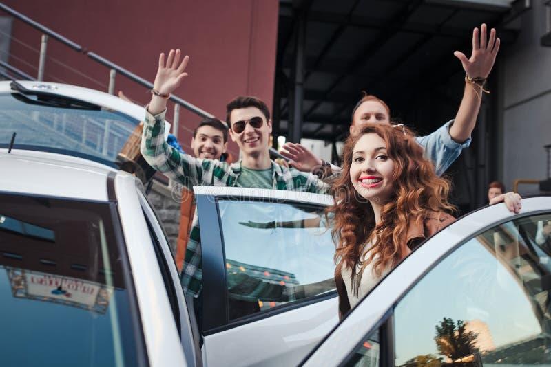 Compañía de cuatro amigos que consiguen en el coche imagen de archivo