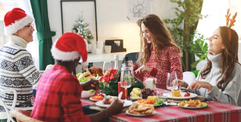 Compañía de los amigos alegres y felices que celebran en la cena de la Navidad imagenes de archivo