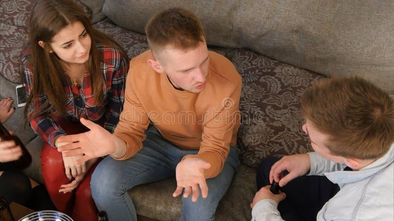 Compañía del estudiante que habla y que se divierte mientras que se sienta en el sofá fotos de archivo libres de regalías
