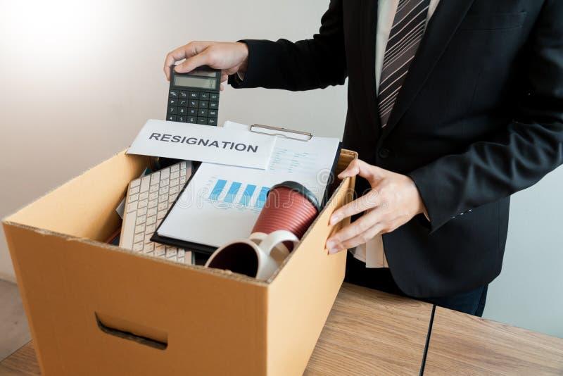 Compañía personal que embala que lleva del empresario en la caja de cartón marrón y cartas de dimisión para abandonado o cambio d fotos de archivo