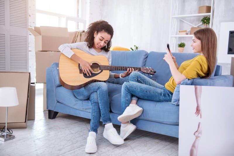 Compañero de cuarto agradable de la grabación de la chica joven que toca la guitarra imagen de archivo libre de regalías