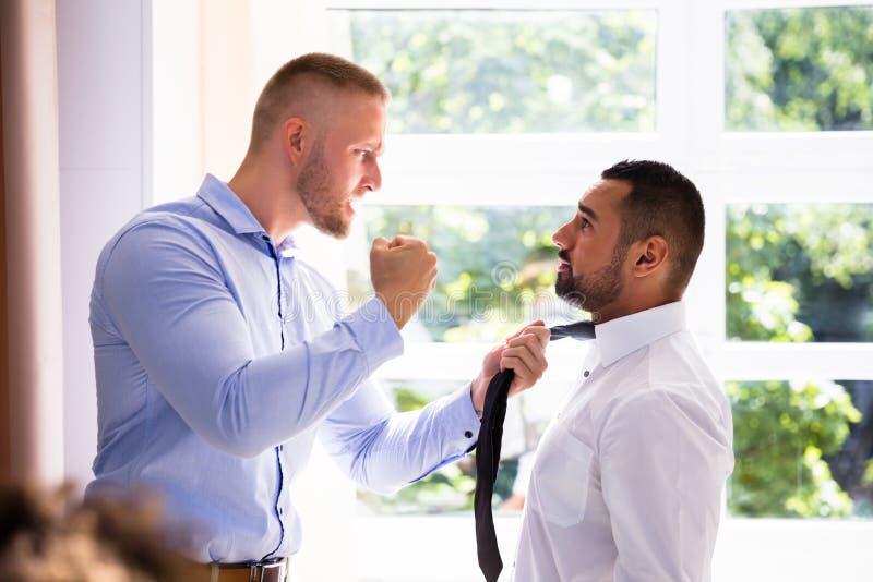 Compañero de trabajo enojado de Fighting With His del hombre de negocios fotos de archivo