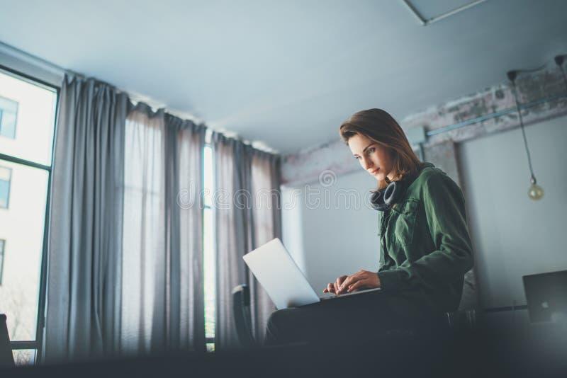 Compa?ero de trabajo femenino hermoso que se sienta en la tabla y que usa el ordenador port?til Trabajo de proceso en el estudio  imágenes de archivo libres de regalías