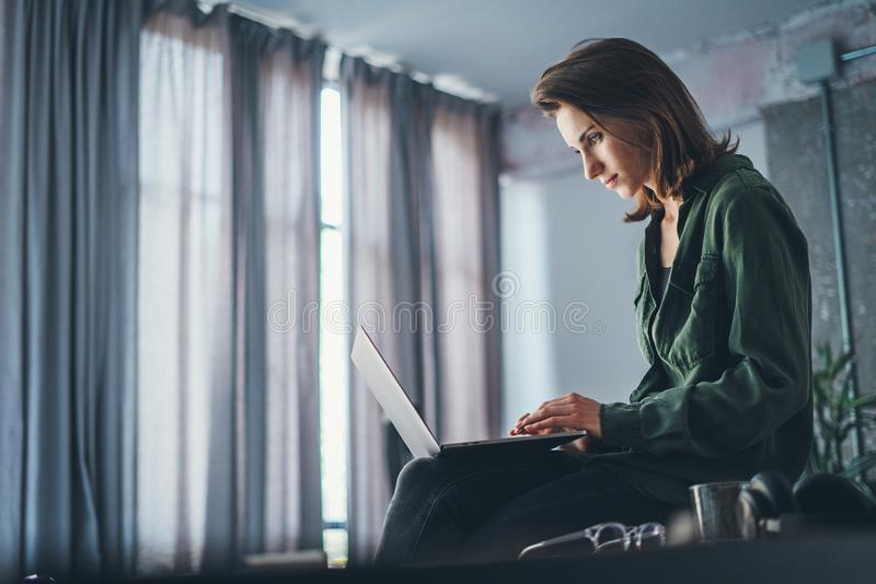 Compa?ero de trabajo femenino hermoso que se sienta en la tabla y que usa el ordenador port?til Trabajo de proceso en el estudio  fotos de archivo libres de regalías