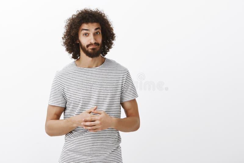 Compañero de trabajo masculino barbudo hispánico apuesto con el peinado rizado en la camiseta rayada, apretando las palmas juntas foto de archivo libre de regalías