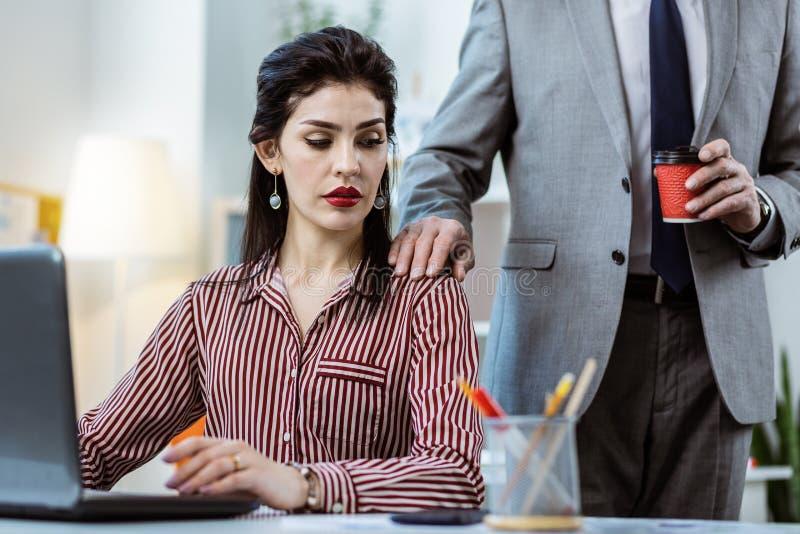 Compañero de trabajo resuelto en el traje gris que pone su mano en el hombro del colega femenino imágenes de archivo libres de regalías