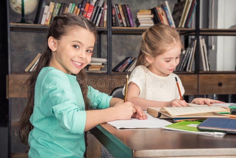 Compañeros de clase que hacen la preparación junta en biblioteca foto de archivo libre de regalías