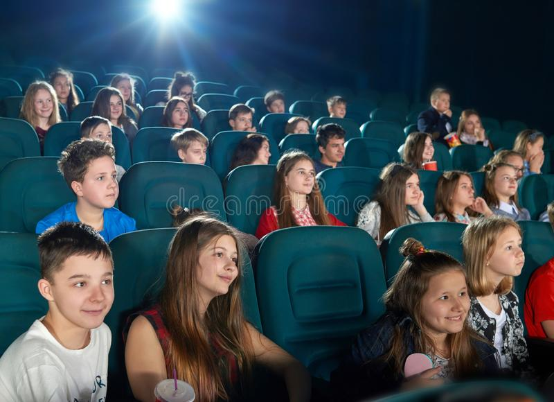 Compañeros de clase que miran la historieta en el pasillo del cine fotos de archivo libres de regalías
