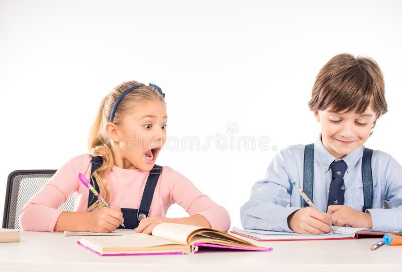 Compañeros de clase que se sientan en la tabla y que estudian junto foto de archivo