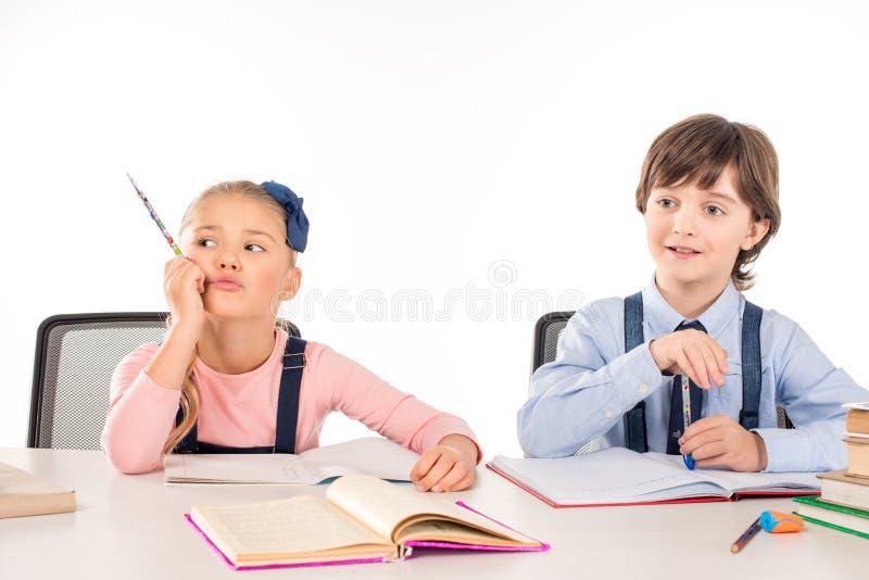 Compañeros de clase que se sientan en la tabla y que estudian junto fotografía de archivo