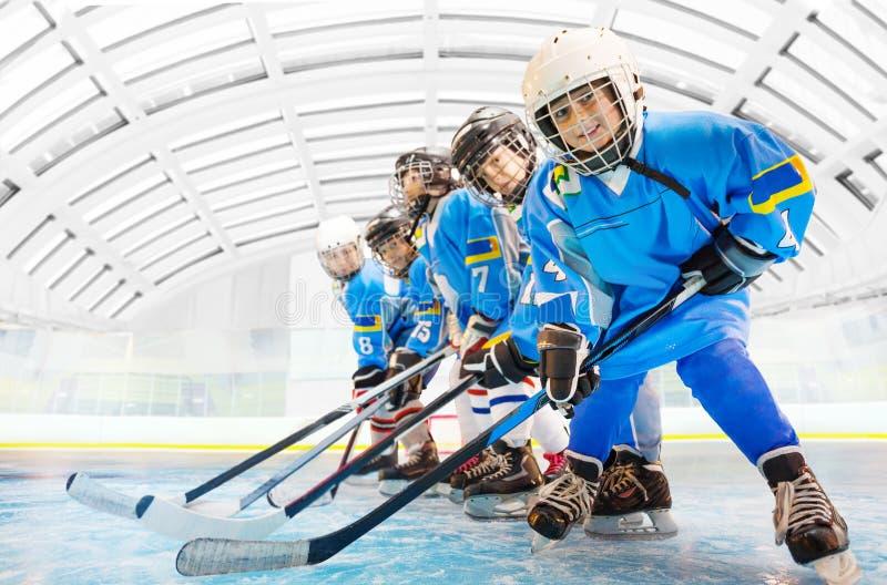 Compañeros de equipo del hockey que se colocan en línea en pista de hielo fotos de archivo