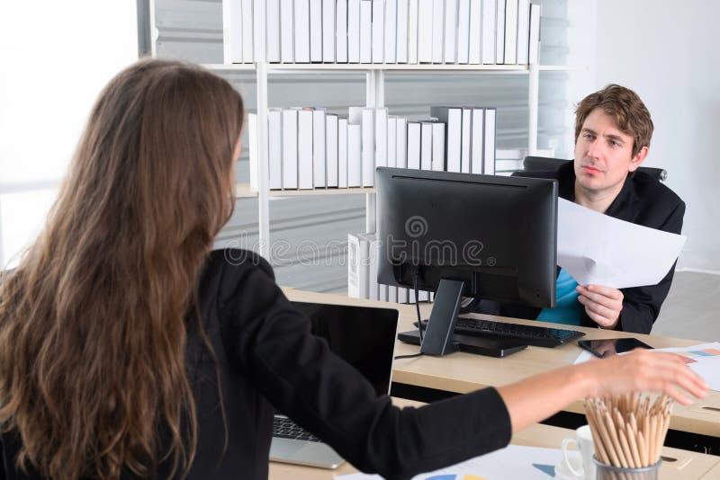 Compañeros de negocios que se reúnen en la oficina principal, o dos jóvenes compañeros de trabajo que trabajan en computadoras po foto de archivo